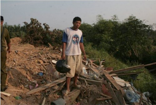 Eigentümer vor Trümmern seines Hauses
